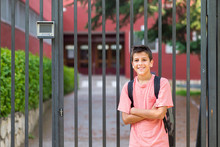 Portrait Of Smiling Student With Backpack Standing Near School Gate