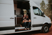 Portrait Of Smiling Couple Sitting In Motorhome