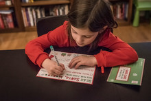 Cute Girl Writing Letter To Santa Claus At Home During Christmas