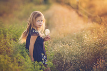 Side View Portrait Of Girl Holding Dandelion While Standing Amidst Plants On Field During Sunset