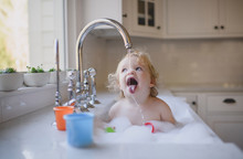 Shirtless Girl Drinking Water From Faucet In Sink At Home