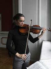 Young Woman Playing Violin At Home