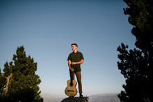 Young Man Holding Guitar While Standing On Rock During Sunset