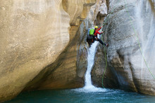 Hiker Rappelling On Pyrenees Over River