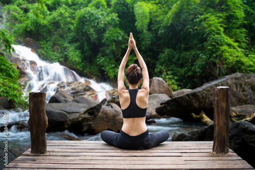Tuinposter Ontspanning Healthy woman lifestyle balanced practicing meditate and zen energy yoga on the bridge in morning the waterfall in nature forest. Healthy life Concept.