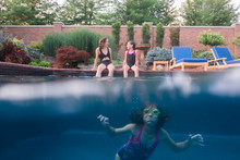 Girl Swimming In Pool While Sisters Talking While Sitting On Poolside