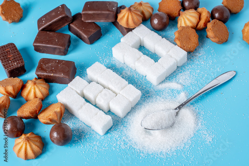 Fototapeta Text No is lined with sugar cubes and sweets. Harm to the health of sweet and rejection of sucrose obraz