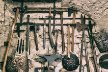 Close-up Of Various Ancient Tools Hanged On Old Wall