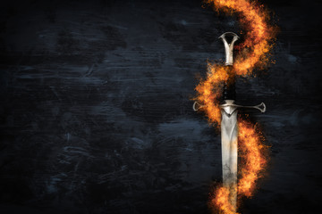 low key image of silver sword in the flames of fire. fantasy medieval period.