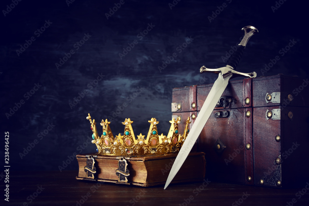 Fototapeta low key image of beautiful queen/king crown over antique book, chest and sword. fantasy medieval period.