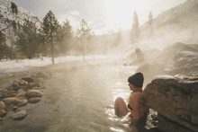 Woman Wearing Bikini Sitting In Thermal Pool At Forest During Winter