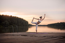 Woman Practicing Yoga On Pier During Sunset