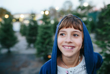 Close-up Of Happy Girl Looking Away While Standing By Pine Tree At Farm During Christmas