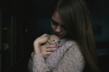 Close Up Of Woman Holding Kitten At Home