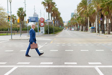 Side View Of Senior Man In Suit Carrying Suitcase While Walking On City Street