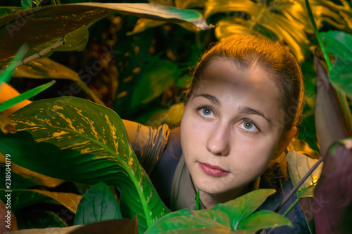 Fotografia, Obraz  young female traveler in rainforest among tropical plants looking up