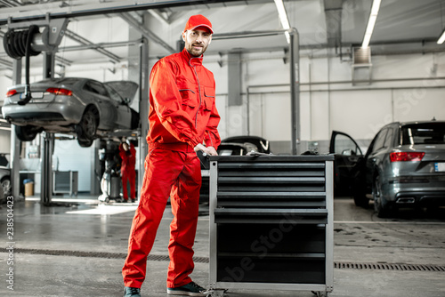 Two auto mechanics in red uniform walking with working cart at the car service