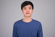 Face of young Asian man against white background