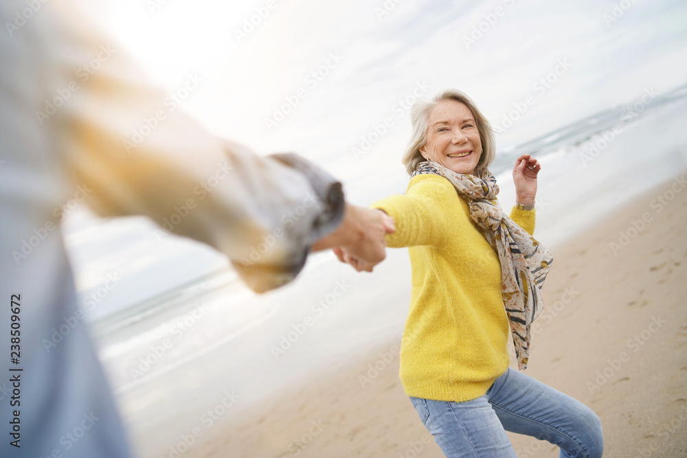 Fototapety, obrazy: Energetic senior woman holding hands with husband in playful manner