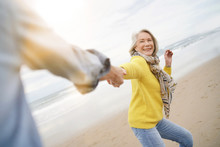 Energetic Senior Woman Holding Hands With Husband In Playful Manner