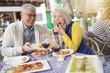 Leinwanddruck Bild - Attractive senior couple eating tapas outdoors