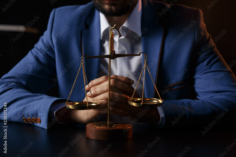 Fototapeta justice and law concept.Male lawyer in the office with brass scale on wooden table,reflected