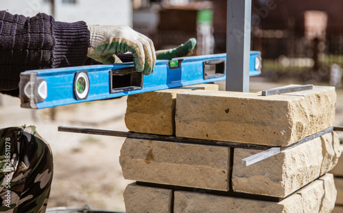 Fototapeta The worker is laying bricks on the fence obraz