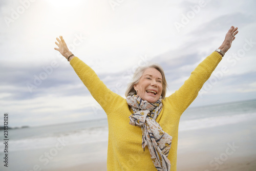 Carefree energetic senior woman playing around on beach in fall Canvas Print