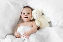 Cute Baby Lying On White Bed With Stuffed Animal