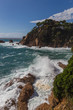 Rocky coastline and crashing waves of the Costa Brava, Spain, against blue sky