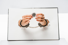 Cropped Shot Of Woman In Handcuffs Holding Bitcoin Through Holes On White