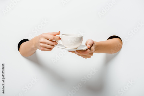 Fotografie, Obraz  cropped image of woman holding cup of coffee and plate through holes on white