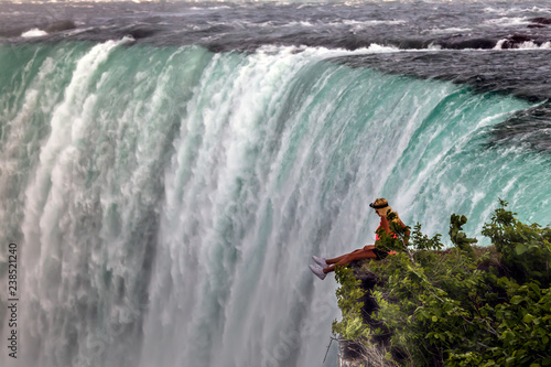 Niagara Falls, Canada. A young women sitting on the edge and looking to the waterfall.