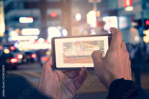 Photo sur Toile Saumon close up of young man hand takes pictures by cellphone on the road in the cityscape with bokeh background