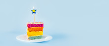 Slice Of Rainbow Cake With Birning Candle In The Shape Of Star On White Round Plate Isolated On Blue Background. Happy Bithday, Party Concept. Wide Banner. Selective Focus. Copy Space.