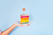 Female Hand Holding White Plate With Slice Of Rainbow Cake With Birning Candle In The Shape Of Star Isolated On Blue Background. Happy Bithday, Party Concept. Square Card. Selective Focus. Copy Space.