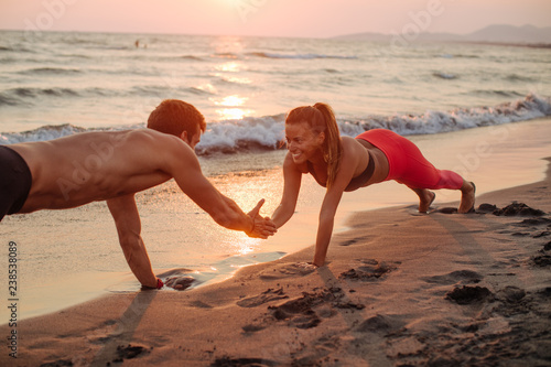 Couple Doing Pushups on Beach