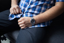 Cropped Photo Of A Strong Man In A Blue Checkered Shirt With Short Sleeves, Dark Jeans For Hours On His Wrist, Sitting On The Sofa And Waiting