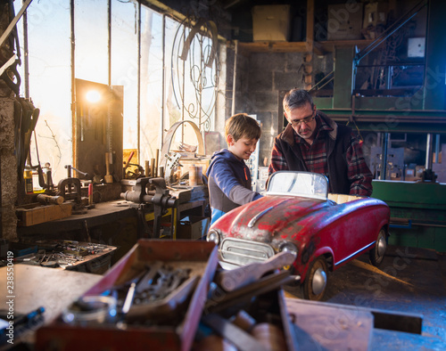 Father and his young son in a DIY workshop to repair a pedal car Wall mural