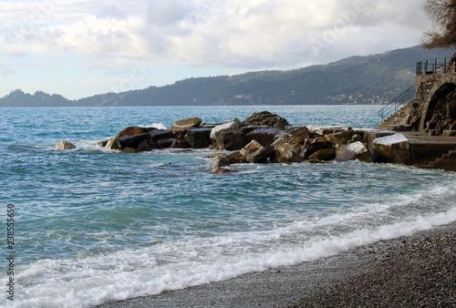 Fototapeta Scogliera frangiflutto con spiaggia e mare agitato