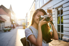 Smiling Young Asian Woman Taking Photos In The City
