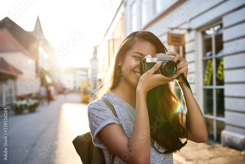 Smiling young Asian woman taking photos in the city Canvas-taulu