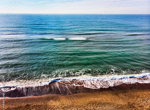 Fotografía  Top view of the beach and a blue and calm ocean with many boats in the distance