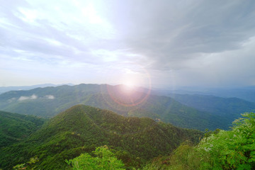 Green mountain and cloudy sky view with sun light flare at the center