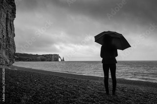 Fotomural femme avac un parapluie sur la plage à étretat sous la pluie