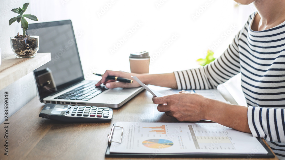 Fototapeta Female accountant calculations, audit and analyzing financial graph data with calculator and laptop Business, Financing, Accounting, Doing finance, Economy, Savings Banking Concept
