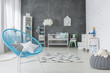 Star pillows on blue armchair in grey baby's bedroom interior with plush toy on pouf. Real photo