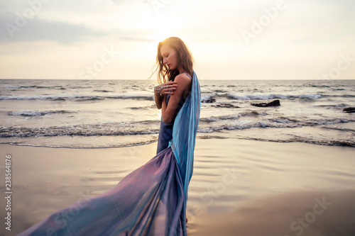 Obraz na płótnie gorgeous style brunette young woman in blue chameleon dress long train standing on a rock near the sea, sand tropical on a rock