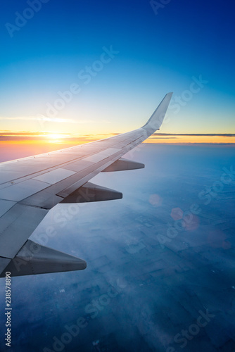 Poster Avion à Moteur Sunset up above the clouds viewed inflight on a passenger airplane.