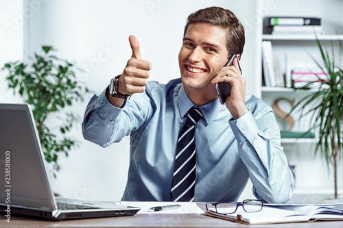 Cheerful businessman talking on the phone and showing thumb up Canvas Print